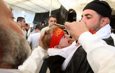 A Shi'ite Muslim taps the head of a baby with a razor to draw blood during a ceremony marking Ashura in Nabatieh, south Lebanon, January 7, 2009.